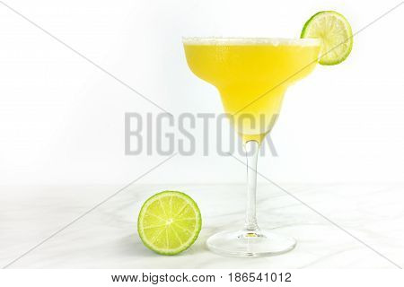 A photo of a lemon Margarita cocktail with wedges of lime and a place for text