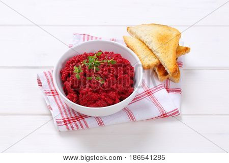 bowl of fresh beetroot puree with toasts on checkered dishtowel