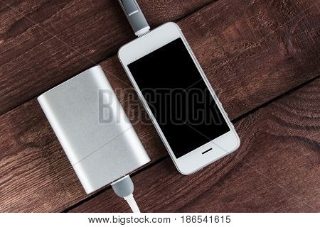 Grey Phone And Power Bank Connected By Cord On Wooden Desk