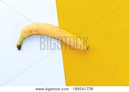Yellow Ripe Banana From The Tropics On A White And Yellow Fabric Background With Space For Text