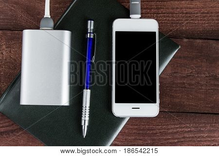 Phone And Power Bank Connected By Cord With Pen And Notebook On A Wooden Background