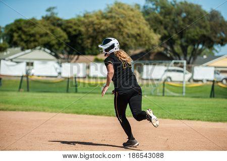 Black uniform softball running around to second base.