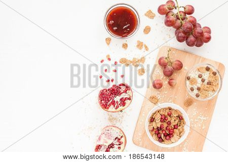 Healthy Breakfast With Yogurt, Muesli, Fresh Fruits And Berries, Cereal, Nuts On White Background. F