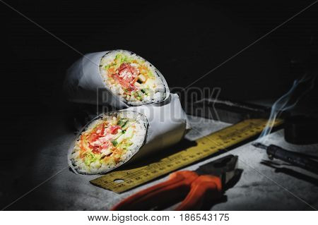 Sea food in roll with pliers, soldering iron and ruler on dark background