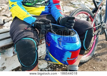 Close-up Male racer mtb cyclist in protective outfit getting ready for race holding full face helmet