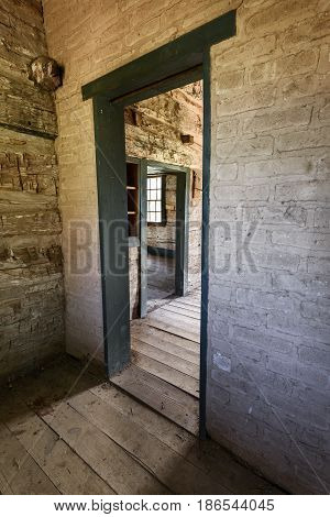 View Through Doorways in Abandoned House with Brick and Log Walls