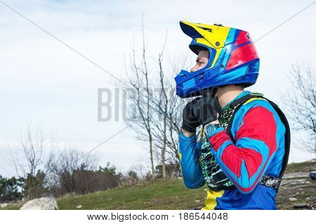 Close-up Male racer mtb cyclist in protective outfit prepares for race clothes full face helmet buttoning on it strap