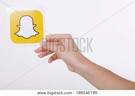 Kiev, Ukraine - August 22, 2016:Woman Hands holding Snapchat logo icon printed on paper. Snapchat is a popular social media application for sharing messages, images and videos