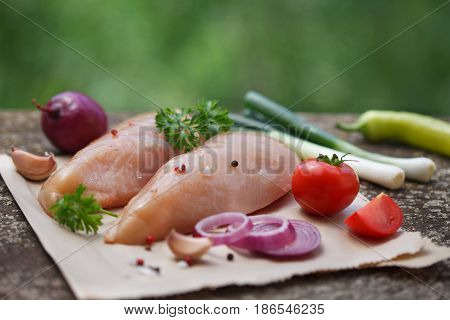 Raw chicken meat fillet on wooden background, rustic style