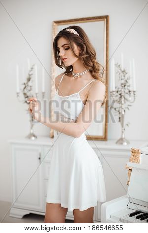 Beautiful sensuality girl wearing in white nightie dress with lace, with wavy hair, shiny asseccories in hair and on neck posing and gesturing. Sexy morning look of attractive woman. Luxury interior.