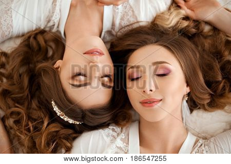 Two beautiful girlfriends in nightie with long wavy hair, lying on bed with closed eyes and smiling. Above view of young sisters with perfect makeup, pure skin, shiny accessories. Morning of couple.
