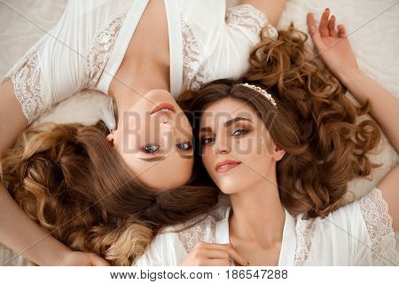 Above view from couple of two beautiful sisters in nightie with long wavy hair, lying on bed and looking, posing at camera. Sensallity girls with perfect makeup and shiny accessories. Bride morning.