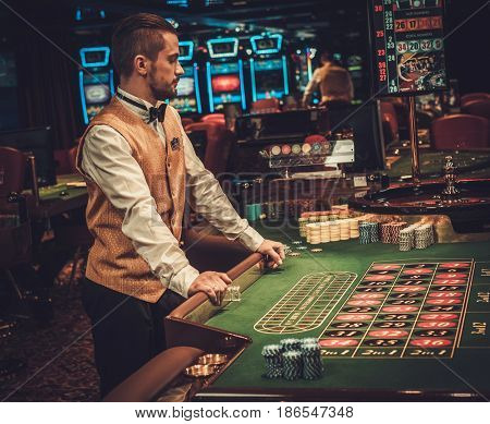Dealer behind table in a casino