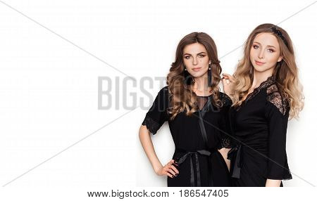 Couple of two sexy women in morning look smiling, holding hand on waist, looking at camera. Seductive beautiful girlfriends posing at studio in black nightie, pajama leaning on wall. Isolate on white.