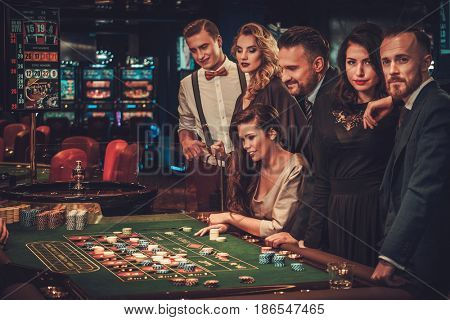 Upper class friends gambling in a casino