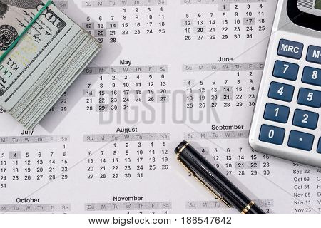 Hundred Dollar Bills With Calendar, Calculator. Close Up.