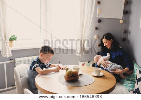 happy young mother having breakfast in kitchen with her baby daughter and kid son