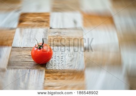 One organic ripe red tomat on surface mosaik board with pieces of different breeds as chess board background. Selective focus. Healthy eating concept, antioxidant and diet