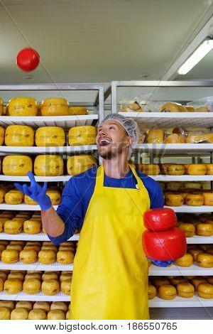Handsome cheesemaker having fun in his workshop storage.