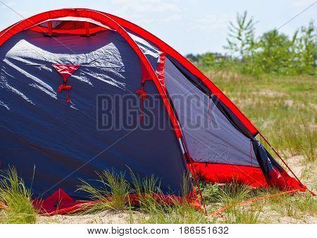 blue tents set tourists on the beach on the sea coast.
