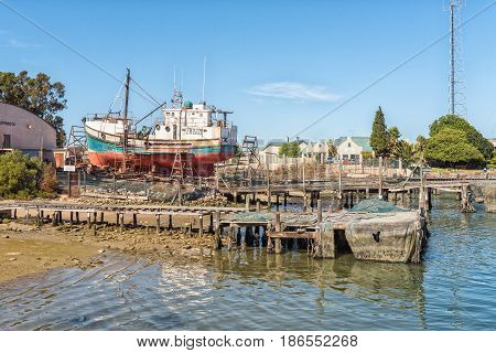 LAAIPLEK SOUTH AFRICA - APRIL 1 2017: A fishing boat being repaired on a slipway at the harbor in the mouth of the Berg River at Laaiplek on the Atlantic coast of South Africa