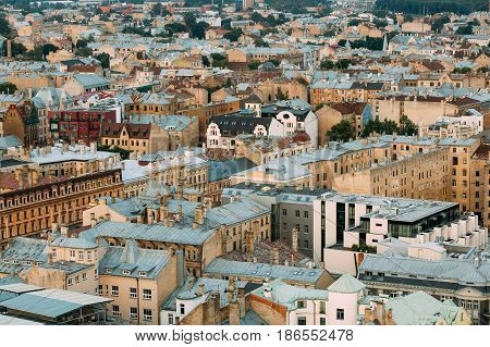 Riga, Latvia. Top View On Old Rusty Roofs Old Houses In Summer Evening