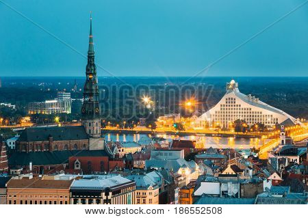 Riga, Latvia - July 2, 2016: Aerial View Of Cityscape In Summer Evening Or Night Lights Illumination. Top View Of St. Peter's Church And Latvian National Library. Blue Hour