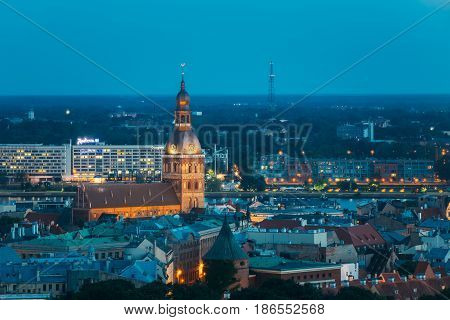 Riga, Latvia - July 2, 2016: Aerial View Of Cityscape In Summer Evening Night Lights Illumination. Top View Of Riga Dom Dome Cathedral. Famous Church And Landmark. Blue Hour