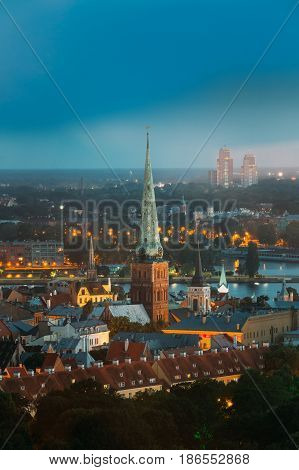 Riga, Latvia. Aerial View Of Cityscape In Summer Evening Or Night Lights Illumination. Top View Of St. James's Cathedral, Or Cathedral Basilica Of St. James At Blue Hour. Wrongly Called St. Jacob's