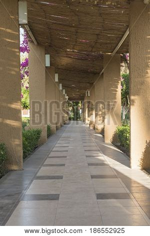 Covered tiled paved footpath pathway with stone columns in rural formal ornamental garden grounds