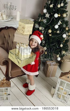 Little girl in santa costume and felt boot holds gifts in room with christmas tree