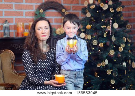Woman in dress and her little son pose with candles near christmas tree in brick room