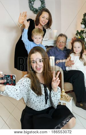 Girl with braces selfies with father, mother, sister, brother near christmas tree, focus on teenager
