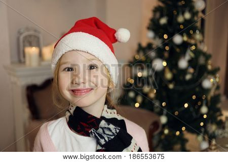 Little cute girl in santa cap and scarf smiles near christmas tree, shallow dof