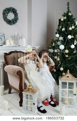 Two little girls in white sit in armchair and depicts hearts in room with christmas tree and lanterns on floor