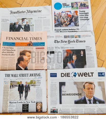 PARIS FRANCE - MAY 10 2017: Multiple international newspapers front page covers with the picture of the newly elected French president Emmanuel Macron the 8th President of France