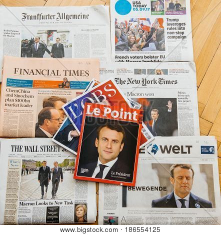 PARIS FRANCE - MAY 10 2017: Le Point magazine above multiple international newspapers front page covers with the picture of the newly elected French president Emmanuel Macron the 8th President of France