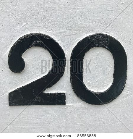 Number 20 twenty two zero silver metal house number address sign screwed into painted white stone wall textured background