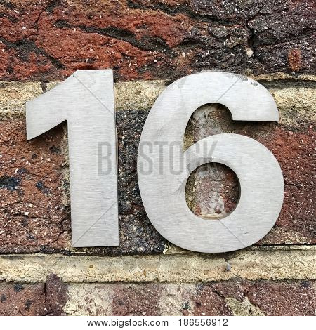 Number 16 sixteen silver metal house number address sign screwed into brick wall textured background