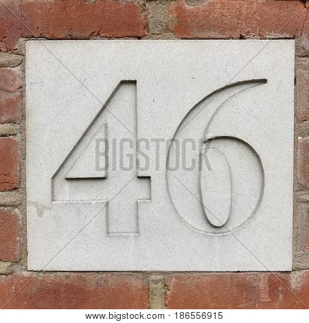 Number 46 forty six carved stone house number address sign screwed into painted white stone wall textured background