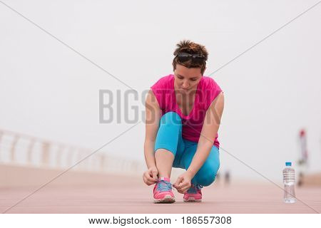 Young woman tying shoelaces on sneakers on a promenade. Standing next to a bottle of water. Exercise outdoors