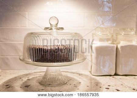 Chocolate cake under a vintage glass cake dome with vintage canisters beside