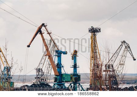 MURMANSK, RUSSIA. Embankment along with the river port, the crane unloads coal