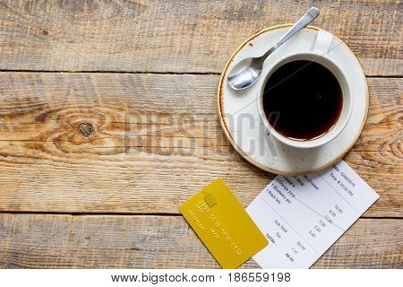 restaurant bill paying by credit card on and cup of coffee wooden table background top view mock-up