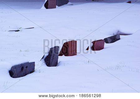 Old vintage colorful grave headstones taken in a cemetery surrounded by snow