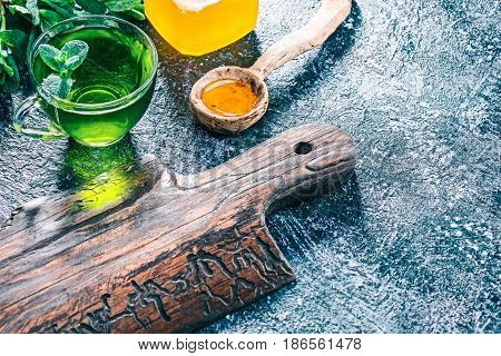 Green mint tea in translucent glass tea cup and honey in rustic wooden spoon on textured spotty background with fresh mint and wooden serving board