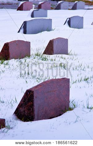 Old colorful grave headstones surrounded by snow taken in a cemetery
