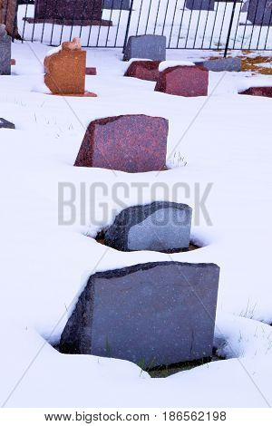 Colorful old grave headstones taken in a cemetery surrounded by snow