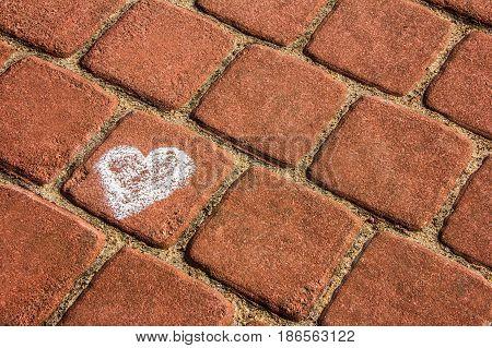 chalk drawing of a heart on the brick sett pavement background