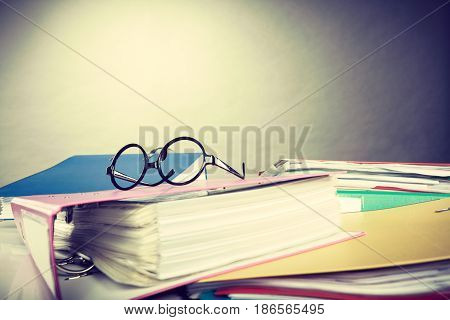 Paper work concept. Piles of colorful binders with many different documents invoice facture. Workplace office of business people.